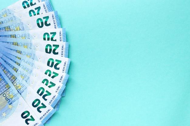 Denaro euro. le banconote da 20 euro sono a forma di ventaglio su uno sfondo blu sul lato sinistro