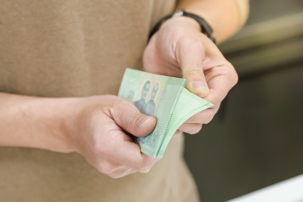 Denaro, finanza e concetto di risparmio. chiuda su della mano dell'uomo che tiene e che conta la banconota di baht tailandese.