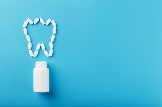 Dente fatto di vitamine bianche con calcio su sfondo blu