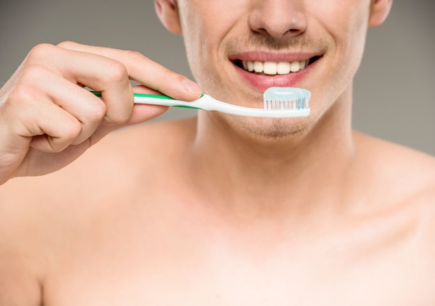 Denti bei di pulizia dell'uomo con lo spazzolino da denti in bagno.