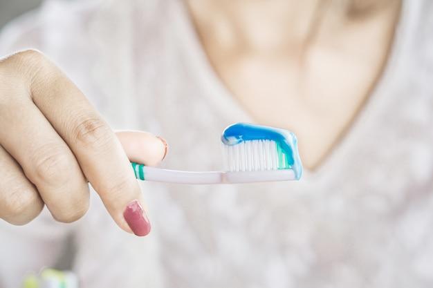 Denti del primo piano della tenuta della mano della donna che tengono spazzolino da denti e dentifricio