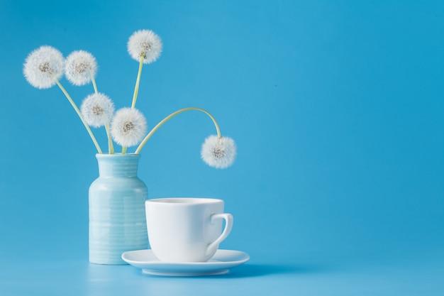 Denti di leone e tazza di tè sul blu