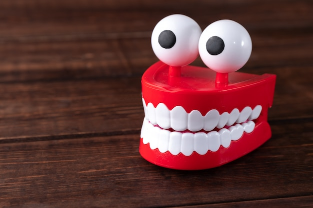 Denti giocattolo con grandi occhi su un tavolo di legno