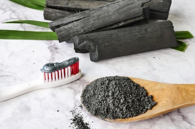 Dentifricio con carbone attivo in polvere sul tavolo di marmo