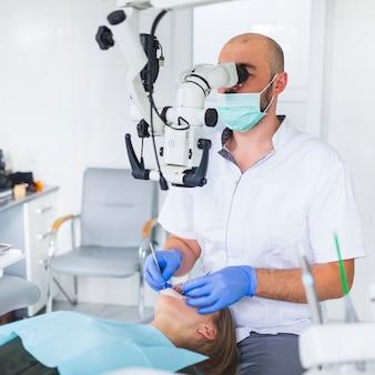 Dentista che esamina i denti del paziente usando il microscopio dentario