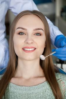 Dentista che esamina i denti di un paziente nella clinica dentale.