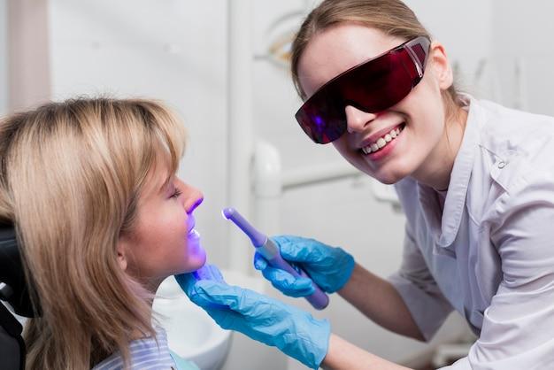Dentista che esegue lo sbiancamento dei denti
