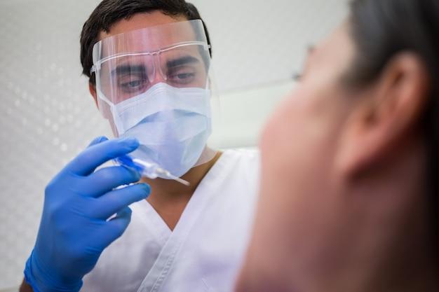 Dentista che fa l'iniezione al paziente femminile
