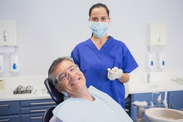 Dentista che indossa maschera chirurgica con un paziente sorridente