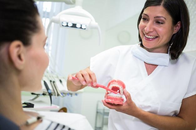 Dentista che mostra al paziente come lavarsi i denti