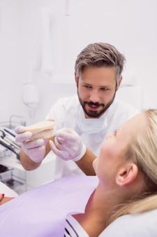 Dentista che mostra il modello della protesi dentaria al paziente