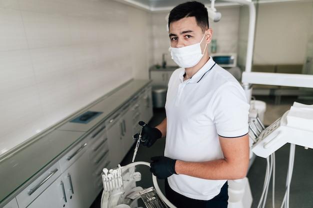 Dentista che posa con l'attrezzatura chirurgica e la maschera