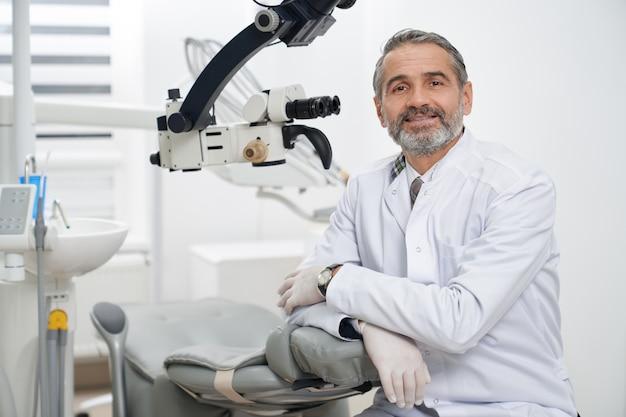 Dentista che posa sul posto di lavoro in clinica moderna.