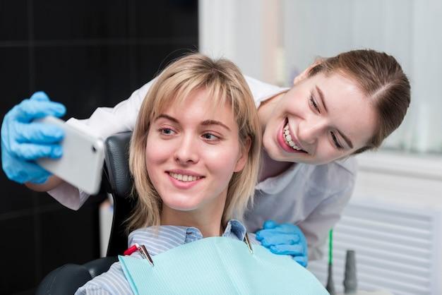 Dentista che prende un selfie con il paziente