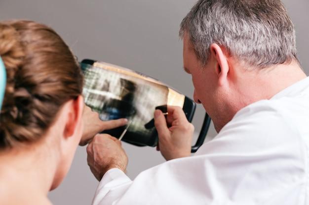 Dentista che spiega raggi x al paziente