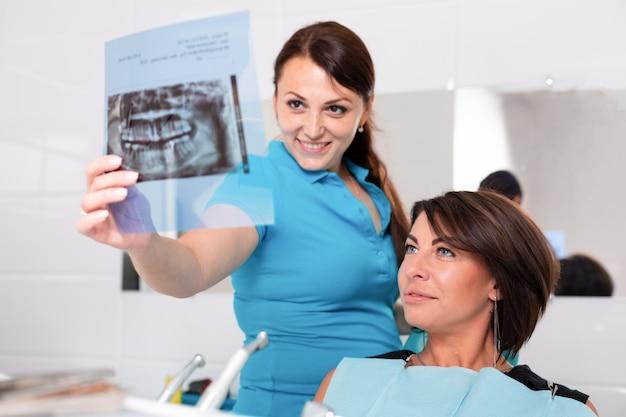 Dentista che termina con successo il restauro dei denti, dottore dai capelli neri, in maschera verde