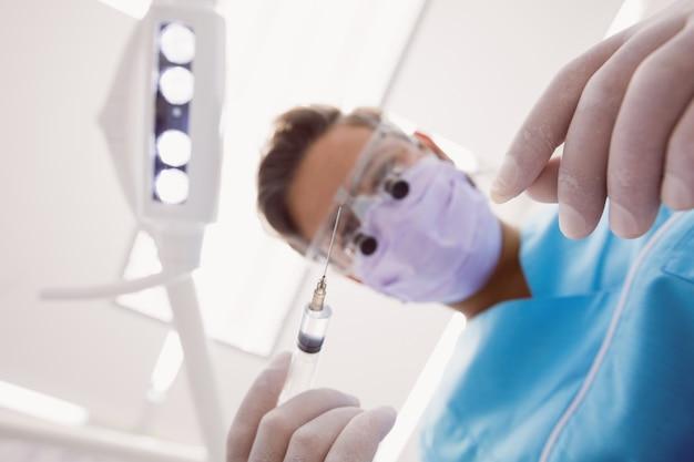 Dentista che tiene gli strumenti dentali