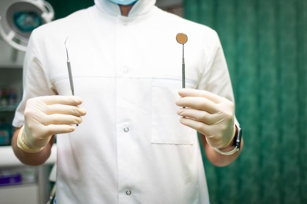 Dentista che tiene il primo piano stomatologico degli strumenti