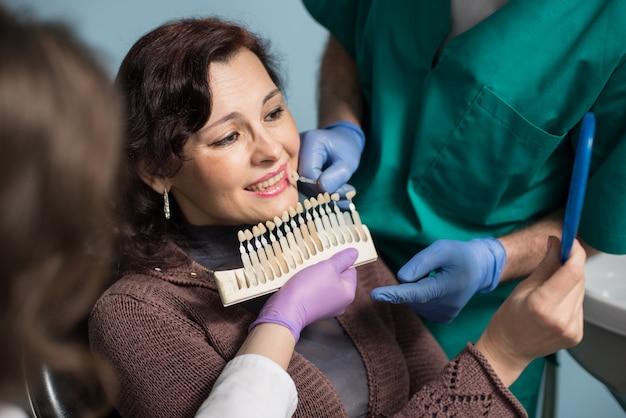 Dentista con assistente e paziente femminile controllando e selezionando il colore dei denti