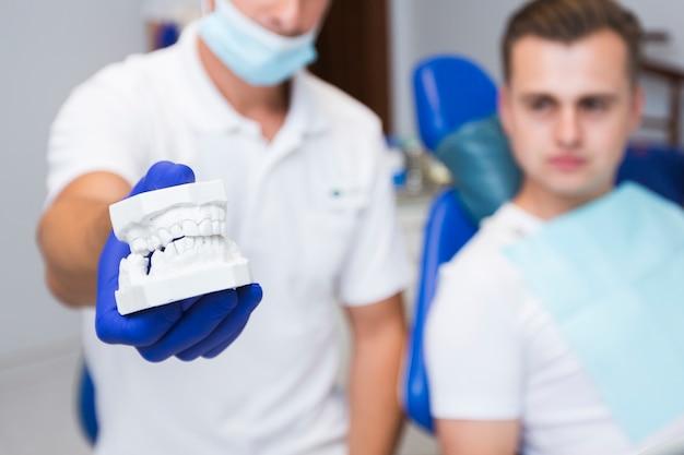 Dentista defocused che tiene le protesi dentarie con il paziente
