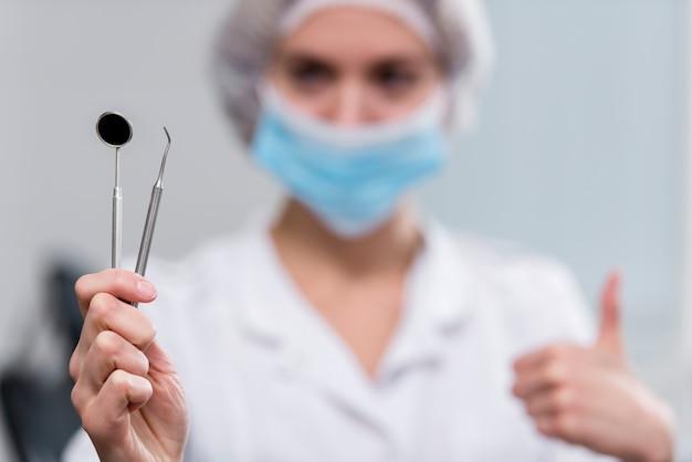 Dentista del primo piano che tiene gli strumenti medici