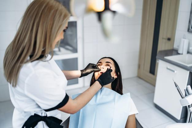 Dentista femminile abbastanza giovane che fa esame e trattamento per il giovane paziente femminile in clinica dentale.