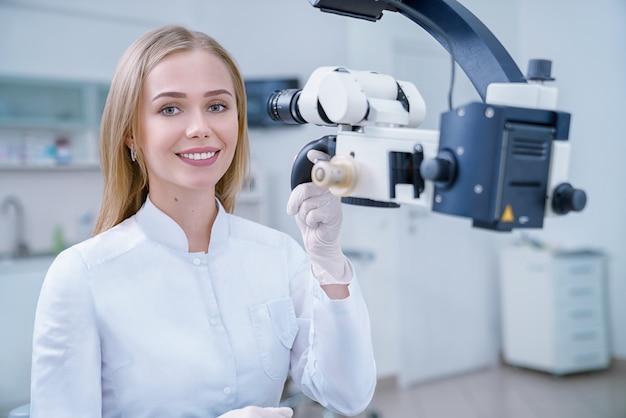 Dentista femminile adorabile che posa e che sorride nella clinica.