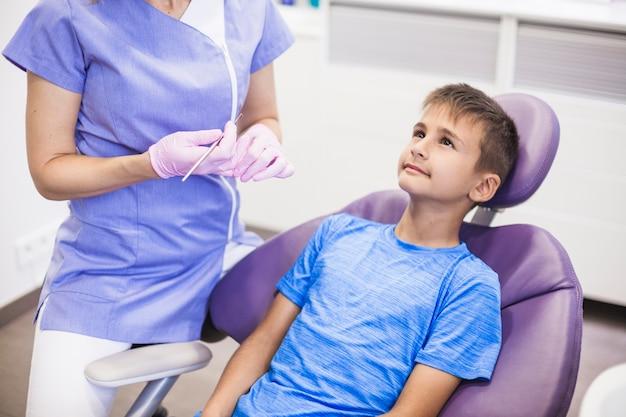 Dentista femminile che sta paziente vicino che si siede sulla sedia dentaria