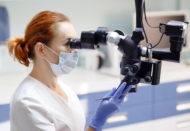 Dentista femminile con strumenti dentali - microscopio, specchio e sonda che trattano i denti dei pazienti presso l'ufficio della clinica dentale, medicina, odontoiatria e concetto di assistenza sanitaria, apparecchiature dentali