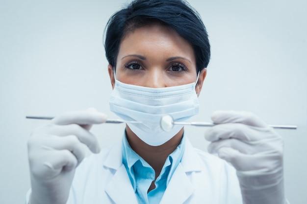 Dentista femminile in maschera chirurgica che tiene gli strumenti dentali