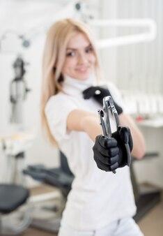 Dentista femminile sorridente con i guanti neri che tengono attrezzatura dentaria all'ufficio dentale. primo piano, messa a fuoco selettiva sugli strumenti. odontoiatria