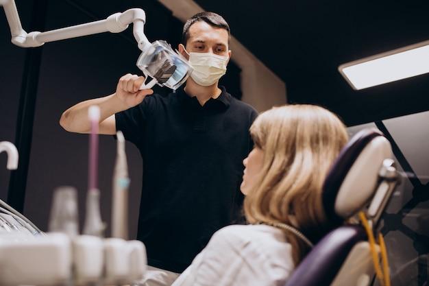 Dentista in visita del paziente della donna