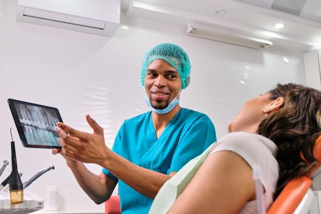Dentista maschio africano che spiega i raggi x al paziente