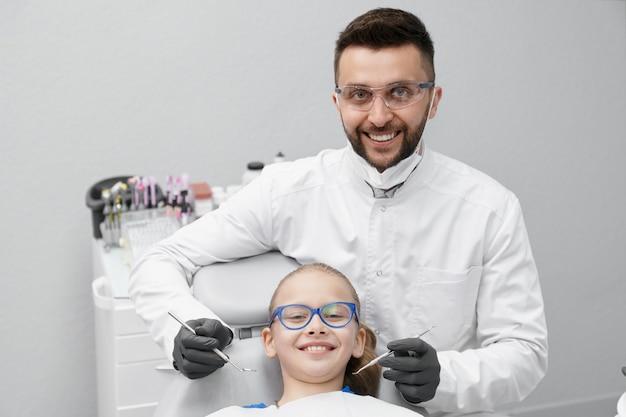 Dentista maschio bello che sorride mentre curando i denti