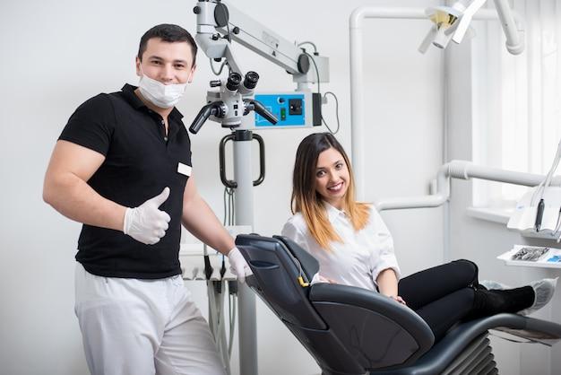Dentista maschio bello con il paziente femminile attraente in studio dentistico moderno. medico che mostra i pollici in su, donna seduta sulla poltrona del dentista. odontoiatria.