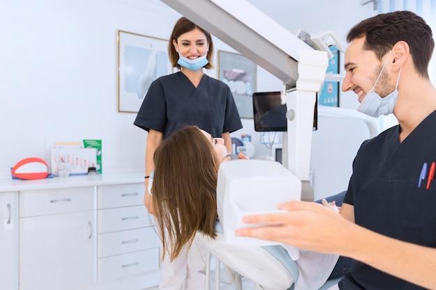 Dentista maschio che esamina i denti del paziente femminile con la macchina dei raggi x