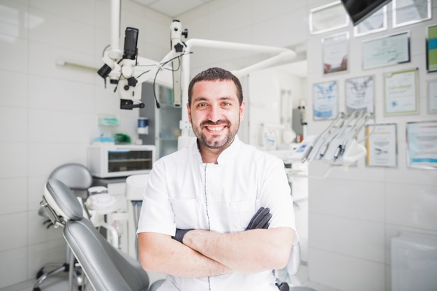 Dentista maschio felice con le mani piegate che guarda l'obbiettivo