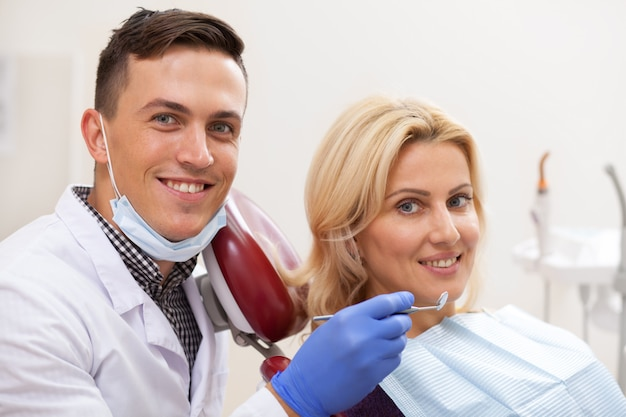 Dentista maschio felice e il suo paziente femminile maturo che sorridono alla macchina fotografica dopo esame dentale. odontoiatria, concetto sanitario
