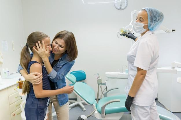 Dentista pediatrico visitante della figlia e della madre alle cliniche dentali