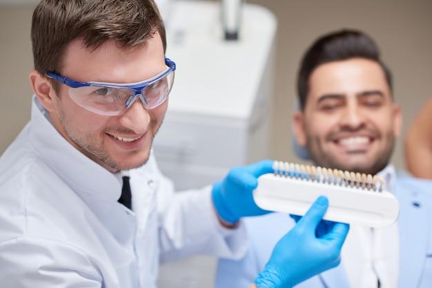 Dentista professionista che sorride mentre lavora con la sua protesi dentaria della tenuta del paziente scegliendo il colore corrispondente per il suo copyspace paziente professionalità occupazione sanità medicina odontoiatria.