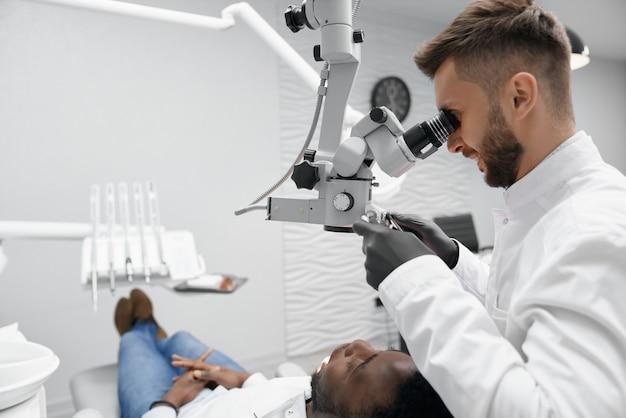 Dentista professionista che tiene attrezzatura e che esamina i denti