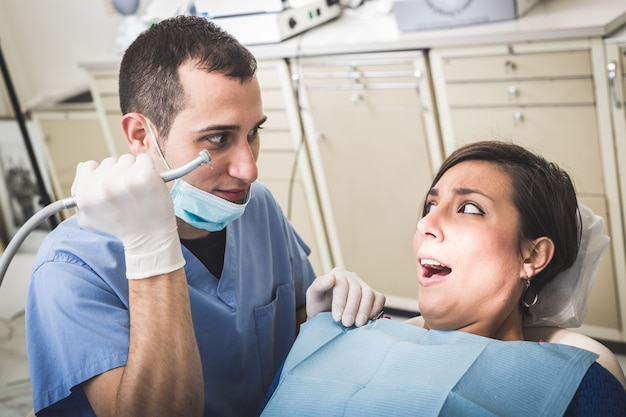Dentista scaring patient with the drill.