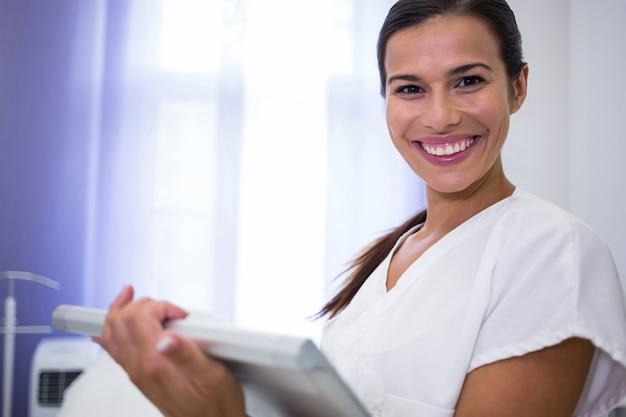 Dentista sorridente che per mezzo della compressa digitale