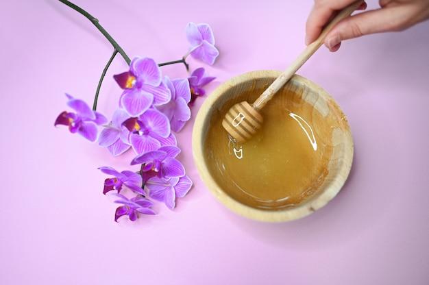 Depilazione ceretta pasta sciolta, orchidea e mano femminile