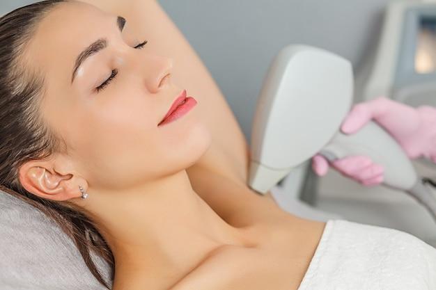 Depilazione laser. primo piano dell'estetista che rimuove l'ascella dei capelli della giovane donna