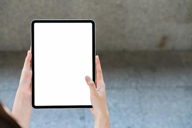 Derida su della mano femminile che tiene lo schermo in bianco della compressa digitale sopra isolato.