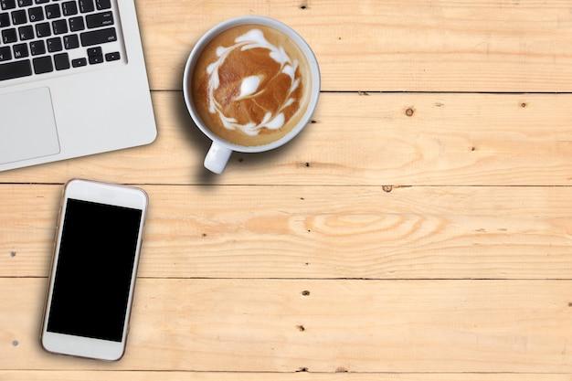 Derida sul telefono cellulare e caffè e tastiera caldi di arte del computer portatile sulla tavola di legno della plancia, spazio della copia