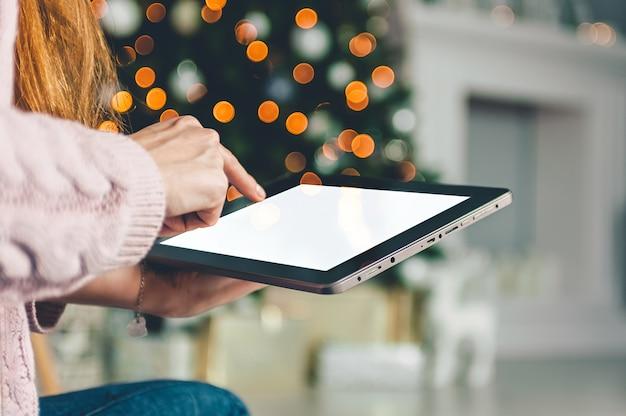 Derida sulla compressa nera nelle mani di una ragazza sullo sfondo, albero di natale del nuovo anno con la decorazione di festa.