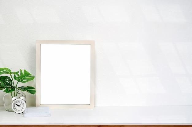 Derida sulla struttura di legno bianca con la pagina in bianco e la pianta da appartamento sulla tavola bianca