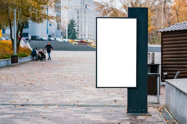 Derisione bianca in bianco su del tabellone per le affissioni verticale della scatola leggera al parco.